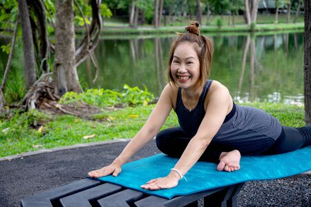 Woman more than 50 year old practicing yoga outdoor location near the lake in the park area. enjoy nice day in nature and positive energy. Happy and smile