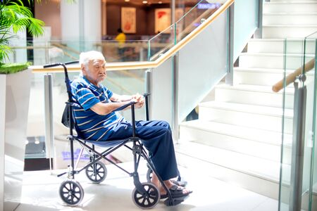 old man sit on wheelchair looking and  fill lonely in the mall waiting for take care,  dementia and alzheimer