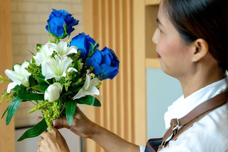 image of flower artist woman working to decorate  artificial flowers decorate on the table with many  color of paper and plastic flower Imagens