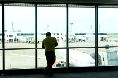 Tourist wait for airplane flight to fly to the point at the window of terminal airport.