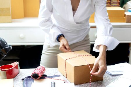 woman  packing a box for  delivery  a product to customer, business owner working checking order to confirm before sending customer in post office, Shipment Online Sales with barcode scanner.
