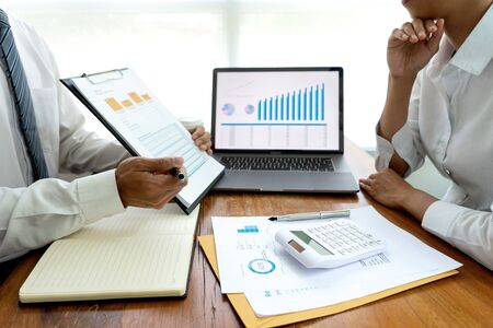business team in casual style have small meeting in the office talk about analyses chart graph marketing plan with computer laptop calculator.