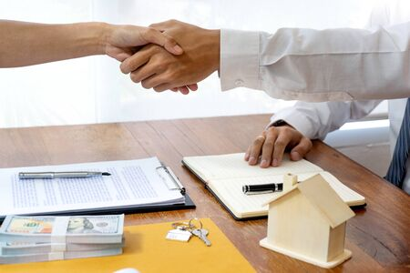 Business talk, Real estate broker agent and customer shaking hands after signing contract documents for realty purchase Standard-Bild