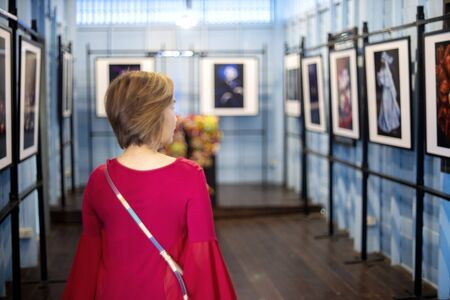 Red dress woman stand and look art the picture in art gallery, blur blue tone room  background. Standard-Bild