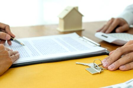 On the table paper sign, a real estate agent prepare home key. For rent or sale house.