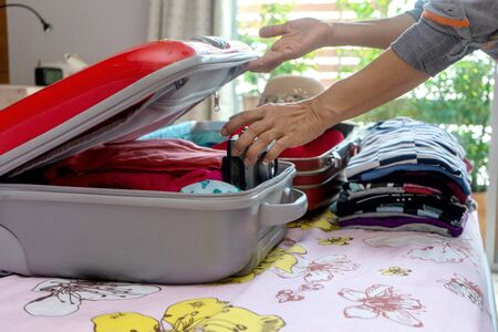 In the room woman pack her luggage for travel vacation time Standard-Bild