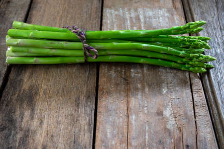 Group of Fresh asparagus on the wood background, raw vegetable food for health cook more copy space.