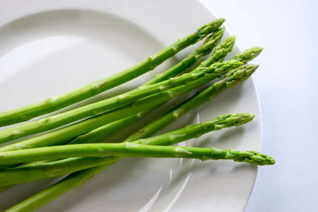 Group of Fresh asparagus on the white dish on light background, raw vegetable food for health cook more copy space.
