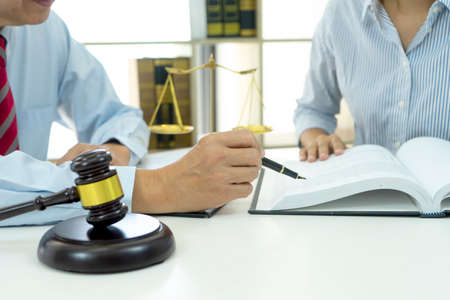 Lawyer or Judge work with assistance  in the office  gavel and balance on the white table.