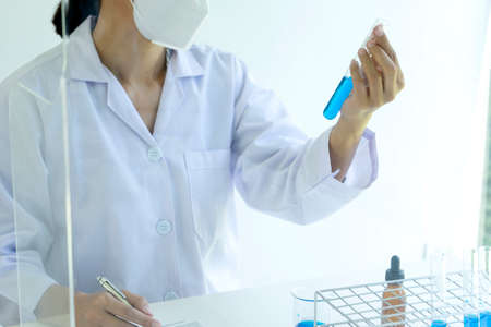 In a chemical laboratory Technician looking at the blue chemical tube on the panorama white background.