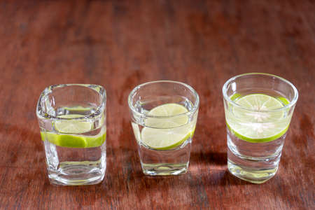 Three Soda water with lemon are in three glass stlye on the wood table.