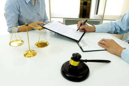 On the table in the lawyer office businessman signature to the contract on the clipboard white copy space with balance and gavel.