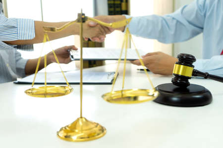 Law concept in the lawyer office businessman give a contract to another and they handshake after finish meeting.