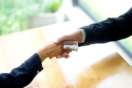 Businessman shake hand with officer and hold the cash in his hand sign to give bribe concept corruption