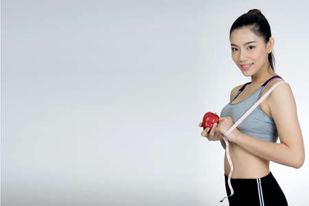 Beautiful sport slender woman with a tape measure and apple in the white background with more copy space