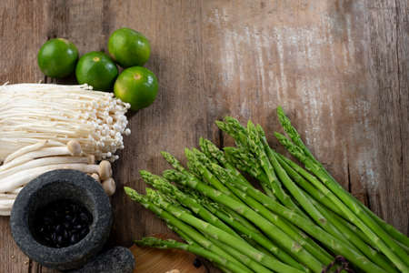 Group of fresh asparagus with golden needle mushroom lemon mortar and black bean  on the wood background with raw vegetable food for health cook more copy space.