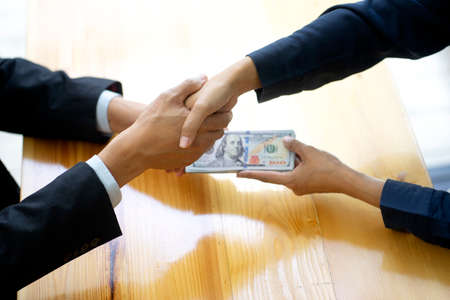 Businessman shake hand with officer and hold the cash in his hand sign to give bribe concept corruption 版權商用圖片 - 162358991