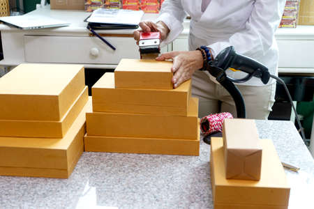 Businesswomen working with box pack to prepare to deliver the product to the customer in the office there is a device for packaging products and barcode scanner