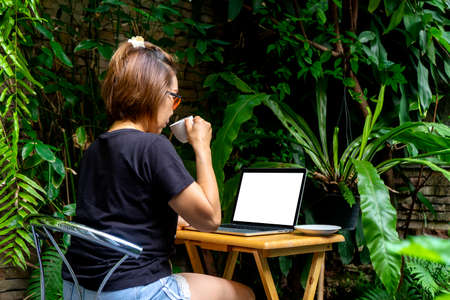 Businesswoman Working on the desk in the green garden at home, concept office work at home away from cover 19 or quarantined. with  white computer  screen computer screen with  clipping path