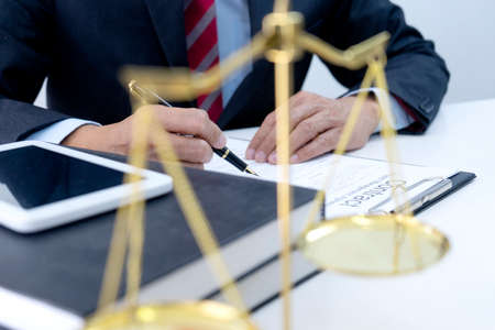 Lawyer write a business contract for businessman in law office on the table there are tablet and balance.