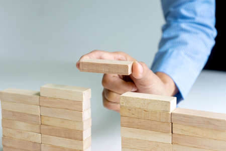 Businessman use wood brick to make wall block it for idea for make business plan image