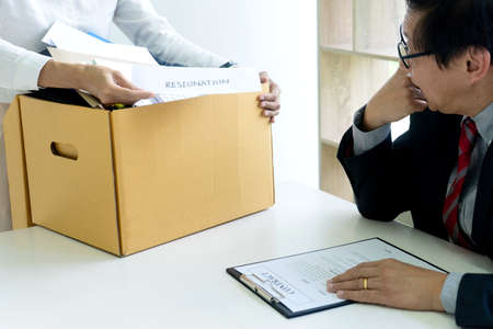 Staff worker hold the box and send resignation letter to boss or manager to tell that she quite from the job Фото со стока