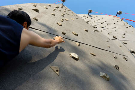 Sportman climbing on the rock wall Sport extreme outdoor mountain climbing