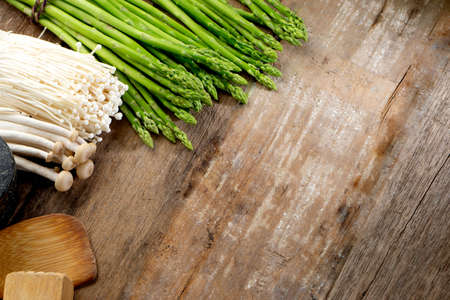 Group of fresh asparagus with golden needle mushroom on the wood background with raw vegetable food for health cook more copy space.