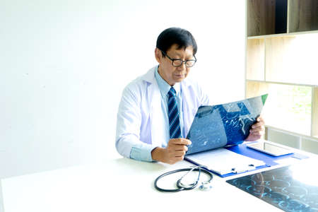 Professional doctor sit and look to mri x-ray film exam case to help patients to have good health in panorama view. 版權商用圖片