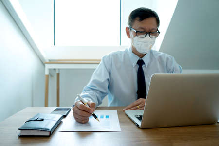 Businessman working in the office he protects himself from the virus covid-19 by use the face mask image focus at the work hand. 版權商用圖片 - 165552672