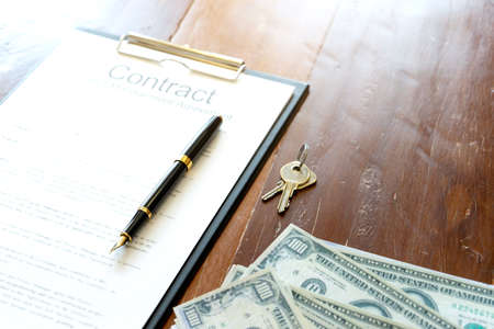 Background image of contract paper are on the wood table with key and cash bank note.