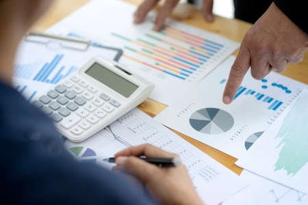 Businessman boss of the team point to graph and chart to reach the target the table for a force to the staff to work hard about the marketing target by use data