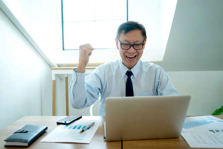the businessman smile  sit in the office arm up to show his feel successful in business way.