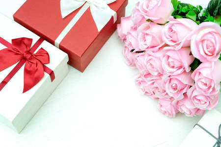 Image of gift box with pink rose on the white table vintage style with more copy space