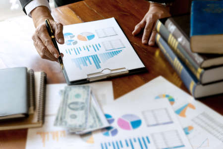 Business people are working considering the graph chart on the table there is cash and books on the table