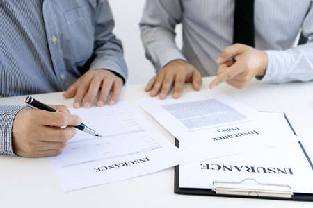 Two businessman sit and sign the insurance document paper on the table