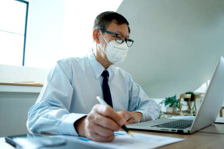 Businessman working in the office he protects himself from the virus   by use the face mask image focus at the work hand. 版權商用圖片