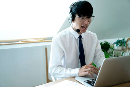Businessmen use the headset to answer the phone with the customer to give the details product or news in the part of telemarketing. Фото со стока