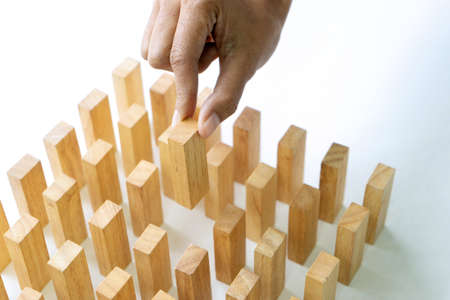 The hand take the wood block on the table for concept to the business strategy.