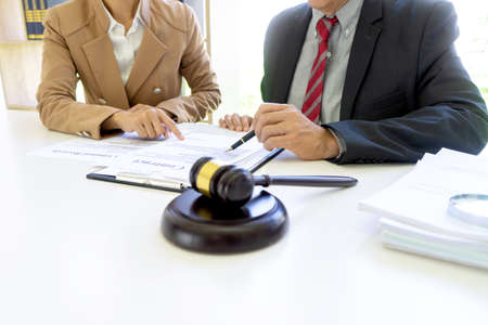 The businesswoman sit and look examined the documents the standing staff presented while working in the office.
