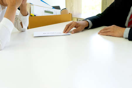 The boss handed a resignation letter of dismissal to the grieving employee on the desk.