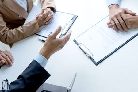 Businessmen are reaching a hand out for a handshake to congratulate job applicants who have passed interviews for the company.
