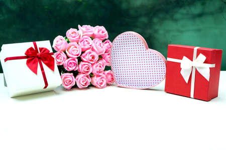 A heart shaped gift box and a red square right box with pink roses placed on a white table.