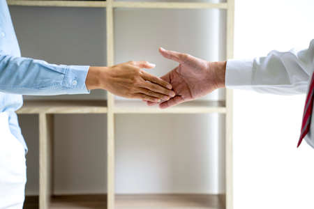 Two businessmen are shaking hands to congratulate them on a successful business deal.