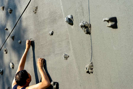 A man climbing on the rock wall sport extreme outdoor in Rock climbing sport gym 版權商用圖片