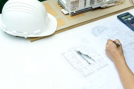 architects or engineer holding pen pointing equipment architects On the desk with a blueprint in the office building model and hat are on the table.