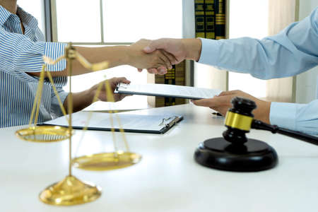 Two business people are handshake  and exchanging a business contract deal in the law firm after finish meeting.