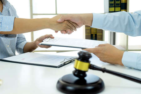 In the law firm, business people are exchanging contracts and shaking hands to congratulate on their success at work. 版權商用圖片