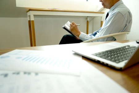 Smart businessman sitting happily thinking on a chair in the office  his hand hold the pen with more copy space. 版權商用圖片