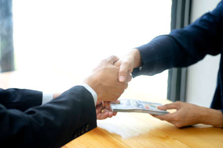 Two businessmen had handshake congratulated the deal and helped with the other hand delivering cash to each other.